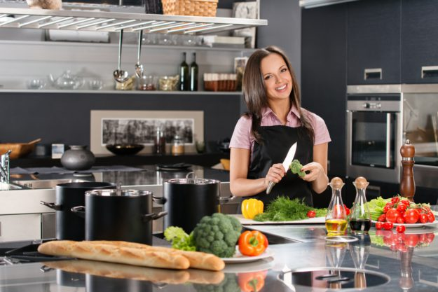 Happy young woman in apron on modern kitchen cutting vegetables