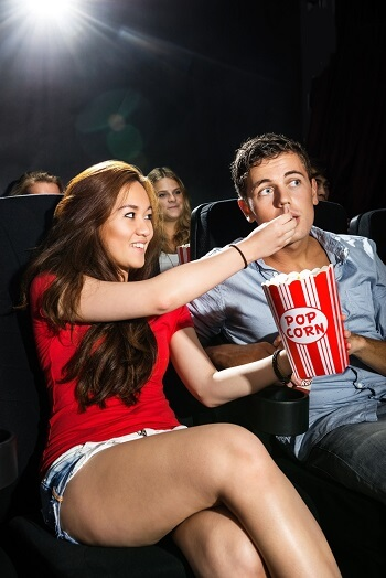 Beautiful young woman feeding popcorn to boyfriend in cinema theatre
